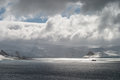 Ship and sunlight in antarctica a floats the distance near snow covered mountains as penetrates a thick bank of clouds Stock Photos