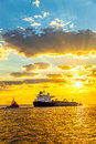 Ship at sunrise tug boat pulling the tanker sea Stock Images