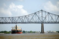 Ship under new orleans bridge container on mississippi river passing railroad in Royalty Free Stock Image