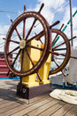 Ship wheel steering of the on blue sky with white clouds Royalty Free Stock Photography