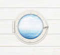 Ship window or porthole on white wooden wall with sea ocean visible through it Stock Photos