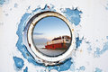 Ship wreck behind round porthole in white and blue wall Royalty Free Stock Images