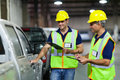 Shipping company workers inspecting vehicle before dispatch Royalty Free Stock Photo