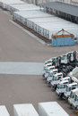 Shipping containers and vehicles at plant metal lined up in rows next to rows of trucks industrial Stock Photo