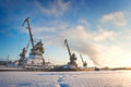 Ships cargo cranes on shore in winter at sunset. Royalty Free Stock Photo
