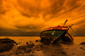 Shipwreck which used to be fishing boat in the sunset Stock Photos