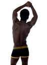 Shirtless african fit guy back pose arms up showing muscles Royalty Free Stock Photography