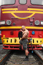 Shirtless athlete stands against locomotive Royalty Free Stock Photo