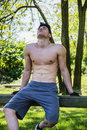 Shirtless athletic young man resting in city park handsome sitting on wood bench Stock Photos