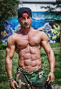 Shirtless bodybuilder showing torso muscles abs pecs and arms outdoors attractive with baseball hat Royalty Free Stock Photography