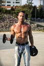 Shirtless hunk man carrying weights gorgeous lifting outdoor snowing healthy body while looking at the camera Royalty Free Stock Photography