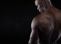 Shirtless male model with copyspace rear view of young man muscular build standing on black background african Stock Image