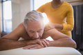 Shirtless male patient lying on bed receiving neck massage from young female therapist Royalty Free Stock Photo
