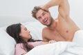 Shirtless man posing next to his sleeping partner men in bed Royalty Free Stock Photos