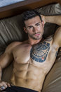 Shirtless sexy male model lying alone on his bed Royalty Free Stock Photo