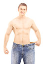 Shirtless smiling male showing his lost weight by putting on an old jeans isolated white background Royalty Free Stock Images