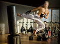 Shirtless young man doing flying kick handsome muscular in gym wearing boxing gloves Royalty Free Stock Images