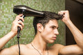 Shirtless young man drying hair with hairdryer Royalty Free Stock Photo