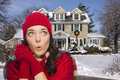 Shivering mixed race woman in winter clothing outside in snow cold looking to the side of decorated house the Stock Photography