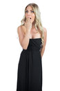 Shocked attractive blonde wearing black dress posing on white background Stock Photography