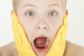 Shocked boy with mouth agape wears rubber gloves Royalty Free Stock Photo