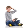 Shocked boy using tablet surprised young sitting on the floor with legs crossed and full length studio shot on white Stock Photos