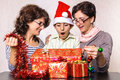 Shocked child boy looking in christmas present box at his toy mother and relative adult women with boxes and decorations around Stock Image