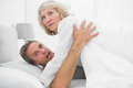 Shocked couple caught in the act at home bed Royalty Free Stock Photography