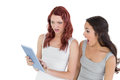 Shocked female friends looking at digital tablet two young against white background Royalty Free Stock Photo