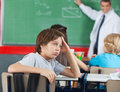 Shocked little boy sitting at desk with classmates and teacher in background Royalty Free Stock Image