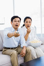 Shocked man and woman at home on couch Royalty Free Stock Photo