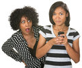 Shocked mother and texting teenager with teenage daughter on phone Royalty Free Stock Photography
