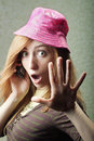 Shocked at news funny young woman in pink hat while gossiping on mobile phone Royalty Free Stock Image