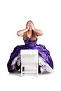 Shocked a pretty caucasian girl wearing a purple ball gown sitting on a white chair and holding her hands over her eyes Royalty Free Stock Images
