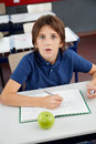 Shocked schoolboy with cheat sheet sitting at desk portrait of little boy in classroom Stock Photos