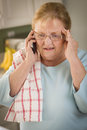 Shocked senior adult woman her cell phone kitchen Royalty Free Stock Photography