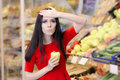 Shocked Woman with Green Pepper Shopping in a Supermarket Royalty Free Stock Photo