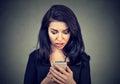 Šokován žena kouká na mobil ustaraný špatný zpráva ona dostal