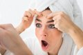 Shocked woman looking at pimple on forehead Royalty Free Stock Photo