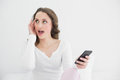 Shocked woman with mobile phone looking away young in bed at home Royalty Free Stock Photos