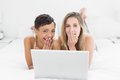 Shocked young female friends with laptop in bed portrait of two at home Royalty Free Stock Image