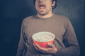 Shocked young man with popcorn a is holding a bowl of Stock Photography