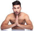 Shocked young man is praying looking away to his side while on white background Stock Photo
