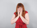 Shocked young woman covering her mouth with her hands Stock Photography