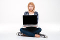 Shocked young woman showing laptop display to camera. Royalty Free Stock Photo