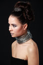 Shocking beauty portrait of cheeky young woman with wire necklac in profile necklace close up bright makeup black background Royalty Free Stock Image
