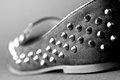 Shoe with studs a black and white close shot of the back part of a flat Stock Photography