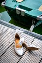 The shoes of the bride lie on the boat dock Royalty Free Stock Photo
