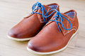 Shoes detail of men s leather with colorful laces on the wooden floor Stock Photography