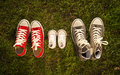 Shoes in father big mother medium and son or daughter small kid size in family love concept three pair of grass park with autumn Stock Photos